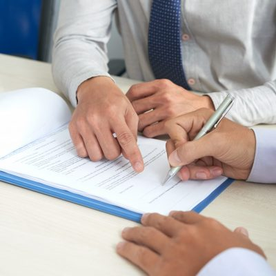 Businessman showing his partner where to sign the contract