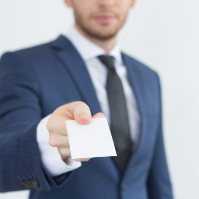 Young financial advisor giving business card. Focus on blank card in hand of businessman. Close-up of card with contacts. Presenting himself concept
